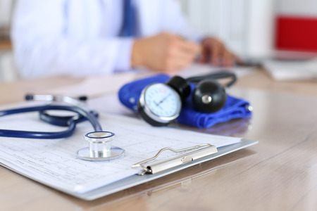doctor clipboard: Medical stethoscope lying on cardiogram chart closeup while medicine doctor working in background.  Stock Photo