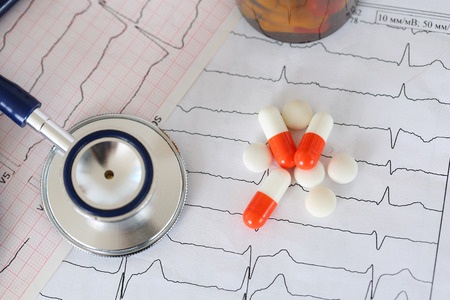prevent: Medical stethoscope head lying on cardiogram chart with pile of pills closeup.  Stock Photo