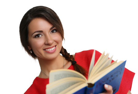 self development: Smiling beautiful woman in red dress wearing plait reading blue book. Female young student holding textbook portrait isolated on white background. Education self development and perfection concept