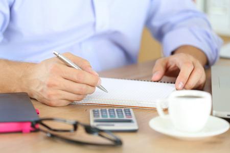 empleados trabajando: Mano masculina que sostiene la pluma de plata listo para tomar nota en el cuaderno abierto.