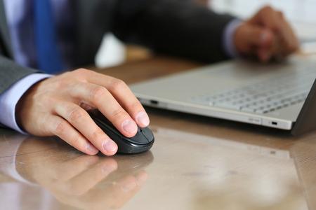 teclado de computadora: Manos del hombre de negocios en traje de la celebración de ratón inalámbrico del ordenador que trabaja con PC portátil.