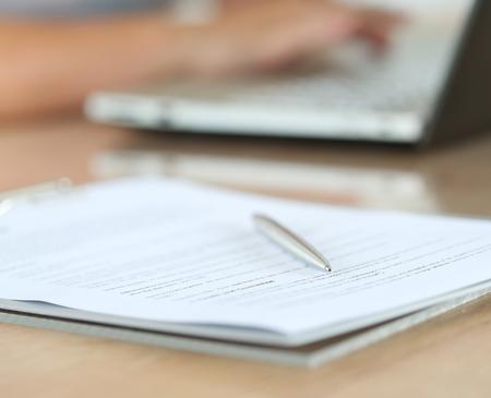 contrato de trabajo: Pluma de plata tirado en el documento de la almohadilla, mientras las manos femeninas que trabaja en la PC portátil en segundo plano.