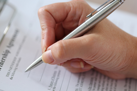 clipped: Hand of businesswoman filling and signing with silver pen partnership agreement form clipped to pad closeup.