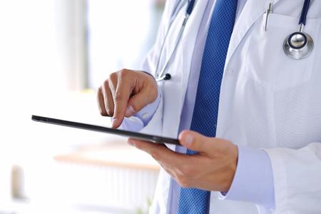sağlık: Erkek tıp doktoru dijital tablet pc tutan ve parmak ile işaret.