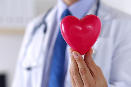 human heart: Masculino medicina médico manos sosteniendo el corazón rojo de juguete delante de su primer pecho.