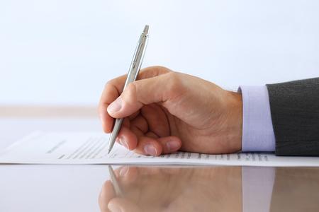 Mano di uomo d'affari in tuta di riempimento e la firma con la forma del contratto penna di occupazione d'argento si trova sulla tabella con la riflessione del primo piano.