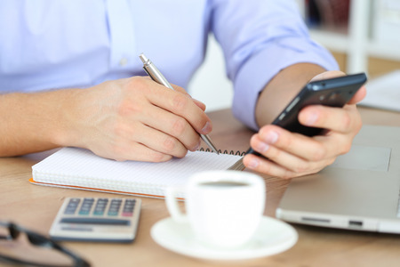 note: Male hand holding silver pen ready to make note in opened notebook while looking at cellphone.  Stock Photo