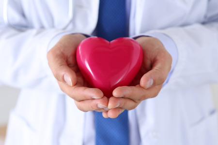 heart hands: Male medicine doctor hands holding and covering red toy heart closeup.  Stock Photo
