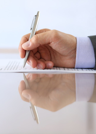 silver reflection: Hand of businessman in suit filling and signing with silver pen employment contract form lying on table with reflection closeup.