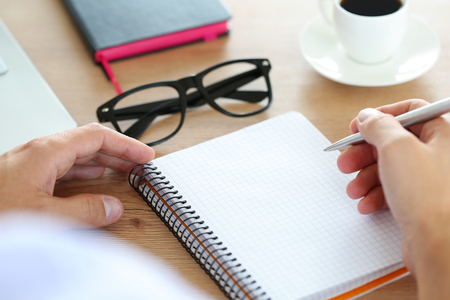 time table: Male hand holding silver pen ready to make note in opened notebook.