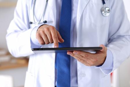 남성 의학 의사 디지털 태블릿 PC를 들고 손가락으로 가리키는.