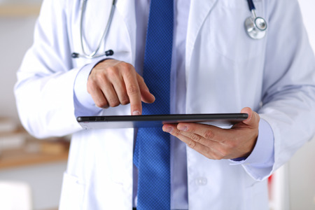 medical practice: Male medicine doctor holding digital tablet pc and pointing it with finger.