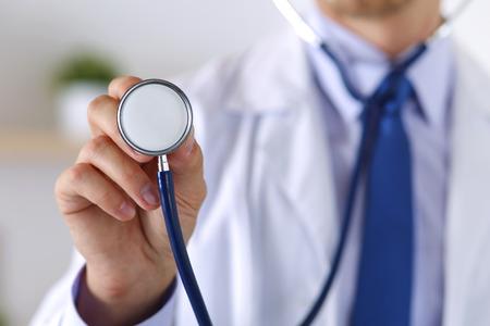 Maschio medicina medico mano che regge stetoscopio testa primo piano di fronte al petto.