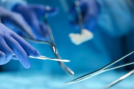 Chirurghi mani che tengono strumento chirurgico durante il funzionamento paziente in sala operatoria. Rianimazione squadra medicina tenendo strumenti medici in acciaio risparmio del paziente. Chirurgia e il concetto di emergenza