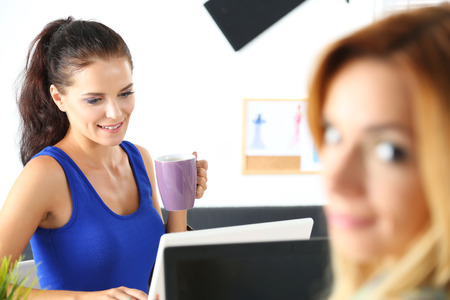 hard day at the office: Two female designers in office drinking morning tea or coffee. Coffeebreak during hard working day. Employee woman holding cup of hot beverage. Creative people or advertising business concept Stock Photo