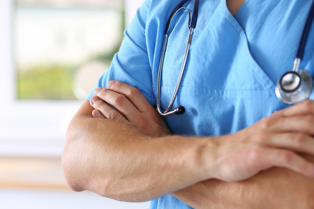 therapeutist: Male medicine therapeutist doctor hands crossed on his chest in office closeup. Medical help or insurance concept. Physician wearing blue uniform waiting for patient to examine Stock Photo
