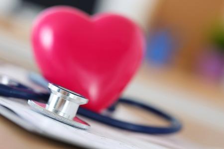 Medische stethoscoop hoofd en rood stuk speelgoed hart liggend op cardiogram grafiek close-up. Medische hulp, preventie, preventie van ziekte of verzekering concept. Cardiologie, gezondheid, bescherming en preventie Stockfoto