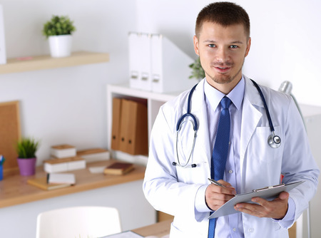 therapeutist: Friendly male medicine therapeutist doctor standing in office, holding document pad and looking in camera. Medical help, physician reception or insurance concept. Physician waiting for patient Stock Photo