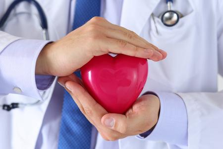 Maschio mani medicina medico in possesso e che coprono rosso primo piano il cuore del giocattolo. Assistenza medica, assistenza cardiologia, la salute, la profilassi, la prevenzione, l'assicurazione, la chirurgia e il concetto rianimazione