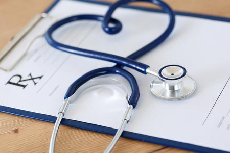 Voorschriftvorm geknipt pad liggend op tafel met een stethoscoop gedraaid in hartvorm. Geneeskunde of de farmacie concept. Lege medische vorm klaar voor gebruik Stockfoto