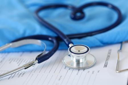 forme et sante: Stéthoscope médical tordu en forme de coeur allongé sur la liste des antécédents médicaux du patient et bleu médecin uniforme agrandi. L'aide médicale ou d'un concept d'assurance. soins de cardiologie, la santé, la protection et la prévention