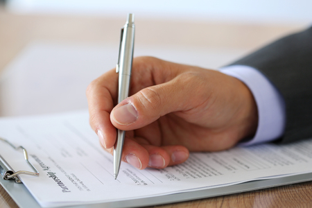 lawyer meeting: Hand of businessman in suit filling and signing with silver pen partnership agreement form clipped to pad closeup. Business success, contract, paperwork or lawyer concept Stock Photo