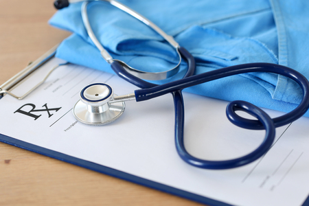 Prescription form clipped to pad lying on table with stethoscope twisted in heart shape and blue doctor uniform closeup. Medicine or pharmacy concept. Empty medical form ready to be used Foto de archivo