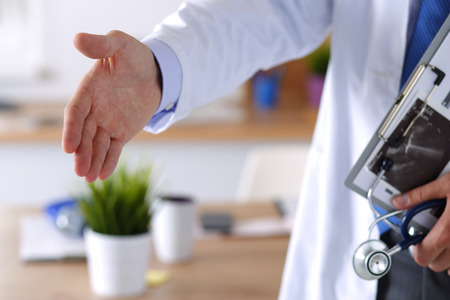 medical treatment: Male medicine doctor offering hand to shake in office closeup. Greeting and welcoming gesture. Medical cure and tests advertisement concept. Physician ready to examine patient