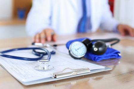 의학 의사 백그라운드에서 작동하면서 심전도 차트 근접 촬영에 누워 의료 청진. 심장 치료, 건강, 보호, 예방 및 도움이됩니다. 건강한 생활 또는 보험