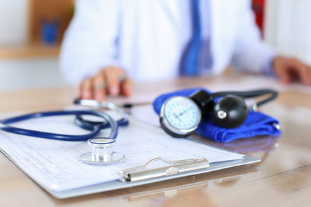 zdravotnictví: Zdravotní stetoskop ležící na kardiogram grafu detailní zatímco lék lékař pracující na pozadí. Kardiologie starat, zdraví, ochrana, prevence a pomoc. Zdravý život nebo pojištění koncept