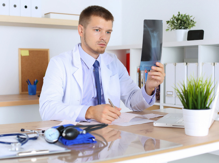 doctor examine: Male medicine physician doctor diagnosing patient with x-ray picture and cardiogram chart sitting at desk in office.  Radiologist, traumatologist or medical insurance concept. Therapeutist thinking Stock Photo