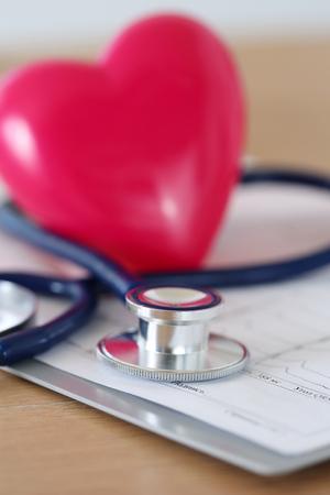 Stetoscopio medica e giocattolo cuore rosso disteso sul grafico cardiogramma primo piano. aiuto medico, la profilassi, la prevenzione delle malattie o concetto di assicurazione. cardiologia, salute, protezione e prevenzione