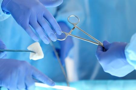 Chirurgen handen houden en het passeren van chirurgisch instrument om andere arts tijdens het besturen van de patiënt. Reanimatie medicijnen teamholding staal medische hulpmiddelen te besparen patiënt. Chirurgie en nood-concept