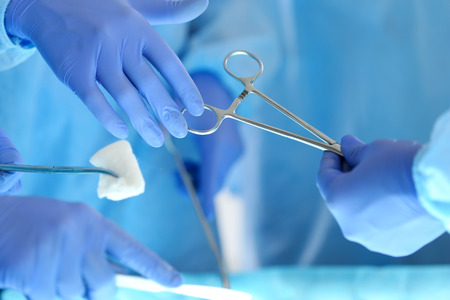 Surgeons hands holding and passing surgical instrument to other doctor while operating patient. Resuscitation medicine team holding steel medical tools saving patient. Surgery and emergency concept Banque d'images