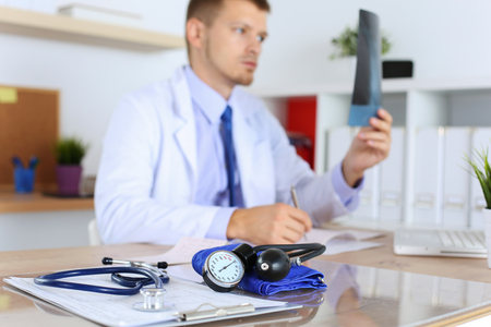 the attack: Medical manometer lying on cardiogram chart closeup while medicine doctor working in background. Cardiology care,health, protection, prevention and help. Healthy life or insurance concept