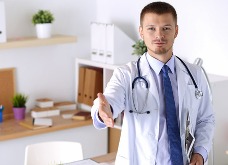 medical cure: Male medicine doctor offering hand to shake in office. Greeting and welcoming gesture. Medical cure and tests advertisement concept. Physician ready to examine patient Stock Photo