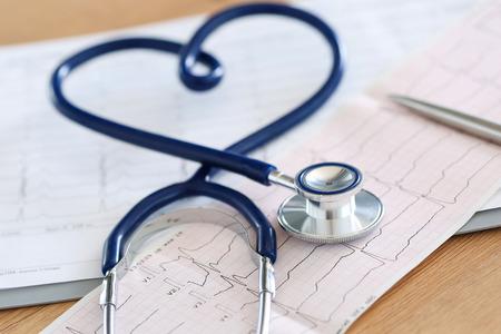Medische stethoscoop gedraaid in hartvorm liggend op cardiogram grafiek close-up. Medische hulp, preventie, preventie van ziekte of verzekering concept. Cardiologie, gezondheid, bescherming en preventie Stockfoto
