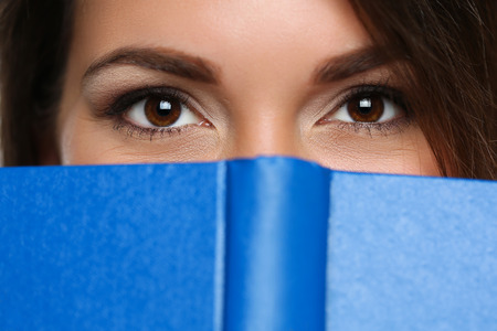 self development: Beautiful brunette woman covering face behind blue book closeup. Female young student holding textbook portrait. Education self development and perfection concept Stock Photo