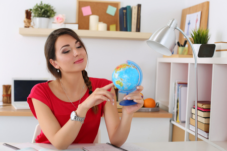 Young beautiful female student pointing something on globe. Geography, politics, culture or history lesson concept. Education, studying, learning, teaching, self development and perfection concept
