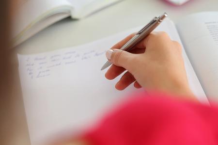 schreibkr u00c3 u00a4fte: Weibliche Hand, die silberne Feder closeup. Woman schriftlich Brief, Liste, Plan, machte sich Notizen, Hausaufgaben machen. Studenten studieren. Bildung, Selbst-Entwicklung und Perfektion Konzept