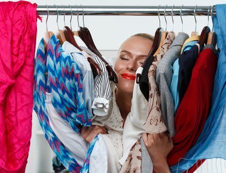 apparel: Beautiful smiling blonde woman standing inside wardrobe rack full of clothes happy to have it. Shopping and consumerism or stylist concept. Nothing to wear and hard to decide concept