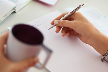 make summary: Female hands holding cup of coffee or tea and silver pen closeup. Woman writing letter, list, plan, making notes, doing homework. Student studying. Education, self development and perfection concept