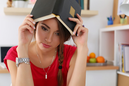 self development: Sad young female student in red dress covering head with book and looking down. Tired woman in despair at workplace suffering because of exam deadline concept. Education and self development Stock Photo