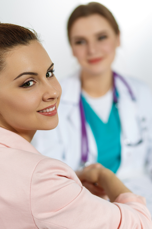 healthcare visitor: Beautiful smiling female patient shaking hands with medicine physician doctor. Partnership, trust, medical ethics concept. Handshake with satisfied client. Thankful handclasp for excellent treatment