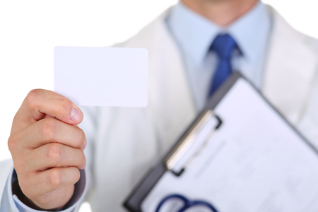 contact information: Male medicine doctor hand holding blank calling card. Physician showing white visiting card in camera closeup. Contact information exchange concept. Introducing gesture at formal meeting Stock Photo