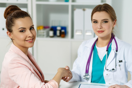 handclasp: Beautiful smiling female patient shaking hands with medicine physician doctor. Partnership, trust, medical ethics concept. Handshake with satisfied client. Thankful handclasp for excellent treatment