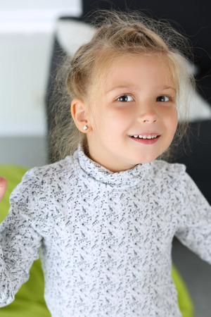 alimony: Amazed little blonde girl looking in camera portrait. Smiling female child with funny face standing and posing. Kid playing games using imagination. Family concept Stock Photo