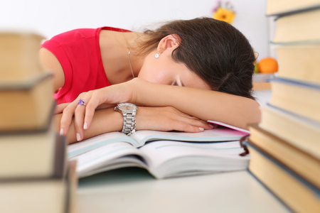 test deadline: Tired female student at workplace in room taking nap on pile of textbooks. Sleepy brunette woman resting during education after sleepless night. Student in despair caused by exam deadline concept