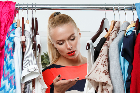 HESITATE: Beautiful thoughtful blonde woman standing inside wardrobe rack full of clothes suffering with choice. Shopping and consumerism or stylist concept. Nothing to wear and hard to decide concept