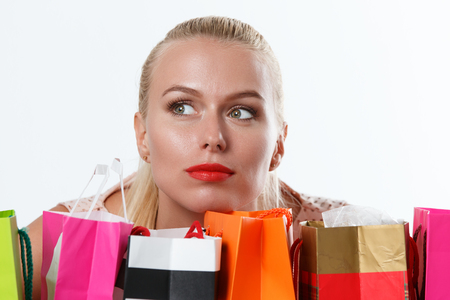 whim of fashion: Beautiful thoughtful blonde woman dreaming with colored paper bags with fresh buyings and presents. Shopping, consumerism and delivery concept. Happy birthday and gifts concept
